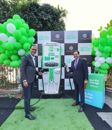 電気自動車用の急速充電スタンドを披露するMGモーター・インディアのラジーブ・チャバ社長(左)ら=同社提供