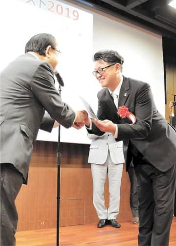 田中復興相(左)から記念の盾を受け取る脇坂さん=東京・霞が関