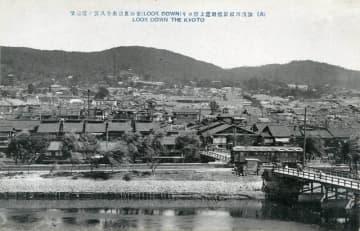 鴨川東岸を走る京阪電車。遠くに清水寺や八坂の塔が写る(宇治市歴史資料館提供)