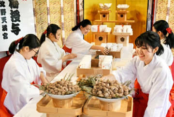 縁起物「大福梅」を紙に包む巫女たち(22日午後2時37分、京都市上京区・北野天満宮)