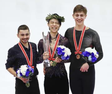 フィギュアスケートのグランプリシリーズ第6戦、NHK杯の男子で3年ぶり4度目の優勝を果たし笑顔の羽生結弦。左は2位のケビン・エイモズ、右は3位のロマン・サドブスキー=23日夜、札幌市の真駒内セキスイハイムアイスアリーナ