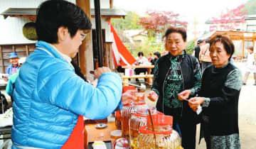 多彩な味の梅酒を楽しむ来場者=吉野川市美郷の東野リキュール製造場