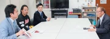 元村長の坂本休さん(右)から話を聞く佐賀県唐津市の関係者=日田市中津江村の鯛生スポーツセンター
