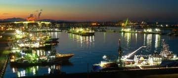 係留された漁船の明かりが輝きを増す夕暮れどきの館鼻岸壁=23日午後4時40分ごろ、八戸市