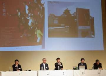 シンポジウム会場のスクリーンに映し出されるチューリップテレビの自社ポスター「正々報道。」=16日、吹田市