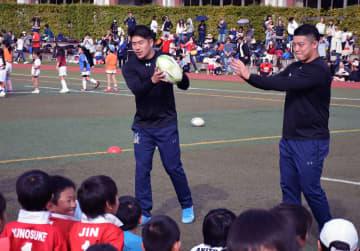 ラグビー教室でパスの基本を伝える松田(中央)と坂手(京都市左京区、同志社中・高グラウンド)