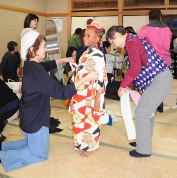 ボランティアに着物を着せてもらい笑顔の子ども=横須賀市総合福祉会館