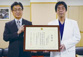 感謝状を手に受賞を喜ぶ青木院長(右)と齊藤事務部長