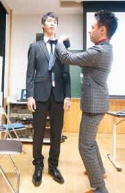 生徒にネクタイの締め方を実演する秋井さん(右)