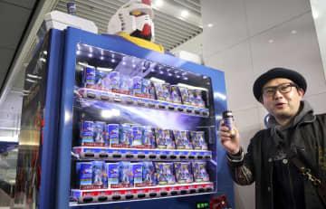 「機動戦士ガンダム」に登場する人型兵器モビルスーツを模した自動販売機で缶コーヒーを購入した男性=25日午前、JR博多駅