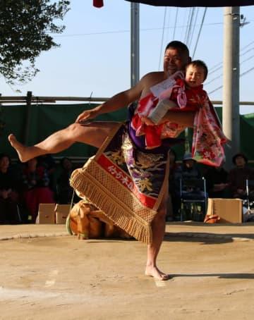 宮相撲大関「竹の本」に抱えられ、泣きだす赤ちゃん=西海市西海町、太田和神社
