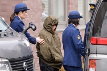 八戸署から青森地検へ送検される久保田良子容疑者(中央)=25日午前9時50分ごろ