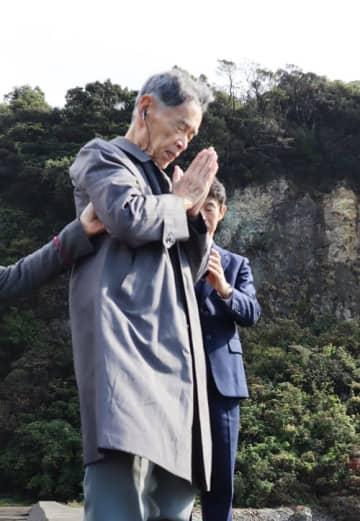 近海丸事故直後に犠牲者らが運び込まれた海岸で手を合わせる宮崎さん=長崎市小江町