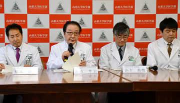 がんゲノム医療拠点病院の機能や意義を説明する山形大医学部の嘉山孝正参与(左から2人目)ら=山形市・同学部