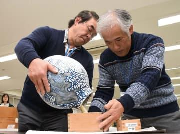 来場者が見守る中、特製つぼを手に計量する中森さん(左)=25日、鳥取市富安2丁目の日本海新聞ビル5階ホール