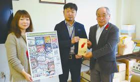 椎名事務局長に寄付金を手渡す岡村さん(中央)