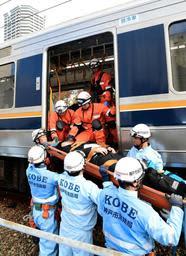 訓練で脱線車両から負傷者を搬送する救急隊員ら=26日午前、神戸市兵庫区駅南通5(撮影・後藤亮平)
