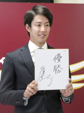 契約更改を終え、来季の目標を書いた色紙を掲げる楽天の岸=26日、仙台市内