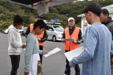 お倉ヶ浜に来たサーファーに、日向市などが事故防止を呼び掛けたキャンペーン