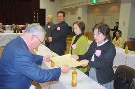 熊谷会長(左)から賞状を受け取る永年勤続者