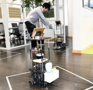 荷物を受け取るロボット(奥)。手前のロボットは状況を認識し、他のロボットと衝突しないよう待機する