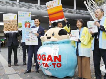 佐賀県内の観光地や県産品をPRする新聞を手にする佐賀県の山口祥義知事(左)ら=27日午前、JR博多駅前