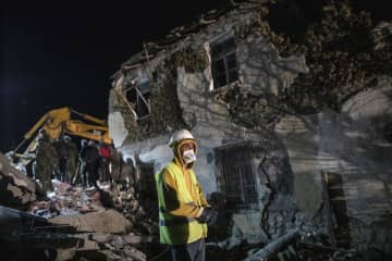 地震で倒壊したビルで救助活動を行う救急隊員=26日、アルバニア北西部トゥマン(AP=共同)