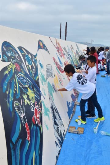 防波堤の壁面にさまざまな絵を描く子どもたち=鴨川市の前原横渚海岸
