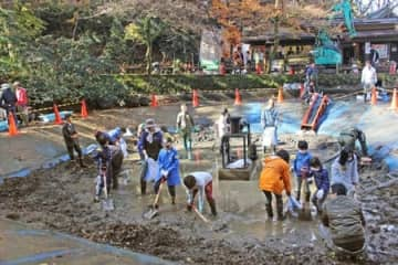 池の底にたまったごみを掃除する親子ら=24日、加茂市