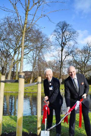 桜の木を植樹する式典に参加した英国日本人会の佐野圭作会長(左)ら=27日、ロンドン中心部(共同)