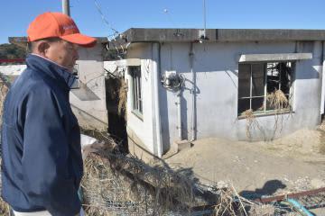浸水被害を受けた用水機場を前にたたずむ蓮田弘さん。フェンスはなぎ倒され、建屋の窓ガラスは破れたままだ=21日午後、常陸大宮市下伊勢畑