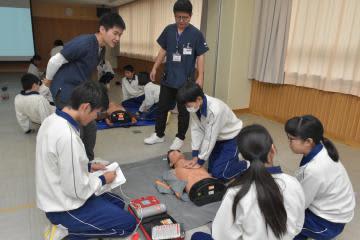 胸骨圧迫とAEDを用いた心肺蘇生法について筑波大生から指導を受ける中学生=筑西市立下館西中