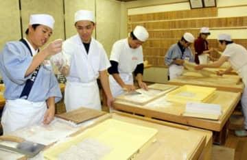 そば打ちクラブで後輩の中学生に助言する中川さん(左から2人目)