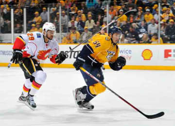 NASHVILLE, TN - APRIL 23: Victor Bartley #64 of the Nashville Predators plays against Akim Aliu #29 of the Calgary Flames at the Bridgestone Arena on April 23, 2013 in Nashville, Tennessee.