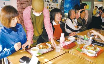 職員に配膳する生徒たち