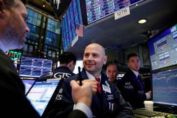 ニューヨーク証券取引所のトレーダーたち=27日(ロイター=共同)