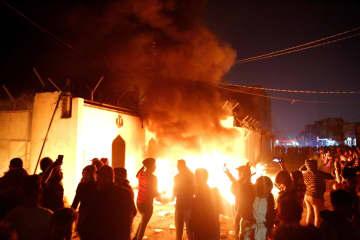 27日、イラク中部ナジャフのイランの在外公館の前で火をつけるデモ隊(ロイター=共同)