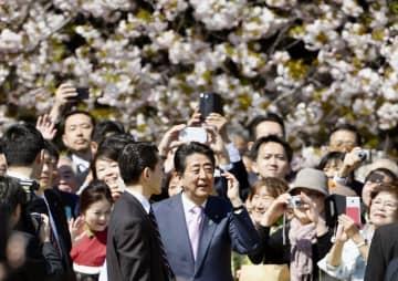 「桜を見る会」で笑顔を見せる安倍首相(中央)=4月、東京・新宿御苑