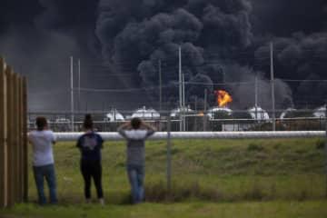 爆発後に黒煙を上げる工場を見守る人々=27日、米テキサス州(AP=共同)