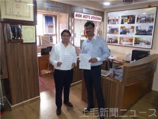 インドの日本語学校とMOUを締結した丸野社長(左)