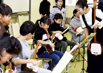 片桐あこさん(右)から三味線を弾くこつを教わる児童たち=11月12日、福井県福井市の松本小学校