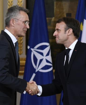 28日、フランス・パリで握手するマクロン大統領(右)とストルテンベルグNATO事務総長(AP=共同)