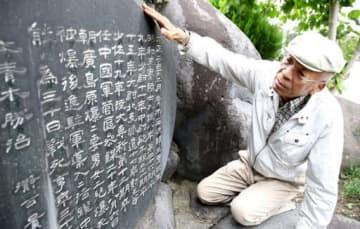 「広島にも家族そろって名前が刻まれ、供養になったと思います」。青木信芳さん家族の慰霊碑に手を添えるおいの久之さん(撮影・河合佑樹)
