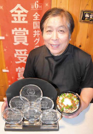 第6回全国丼グランプリで6年連続の金賞を受賞し、トロフィーと豚玉丼を持つ新井和夫さん=秩父市荒川上田野の「たぬ金亭」