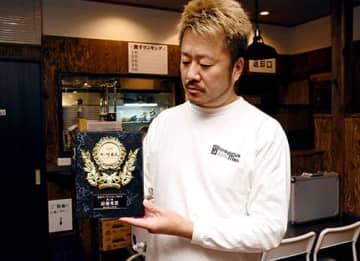 「ザ・仕事人エクセレントアワード2019」最優秀賞の盾を手にする新旬屋の半田新也社長=山形市・「中華蕎麦 ひろた」
