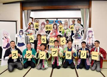 キャラクターパネルと共に記念撮影する山形、秋田、宮城、福島の旅館経営者ら=米沢市