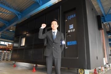 「南極移動基地ユニット」の前で意気込みを示す第61次観測隊員の鈴木聡さん=10月、東京都立川市の国立極地研究所
