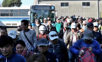 宮崎市の県総合運動公園から出発したシャトルバスで会場の宮崎カントリークラブに到着したギャラリーたち=29日午前