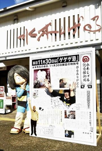 水木しげる記念館前に置かれた「ゲゲゲ忌」のパネルと記念撮影する鬼太郎ら=30日、鳥取県境港市
