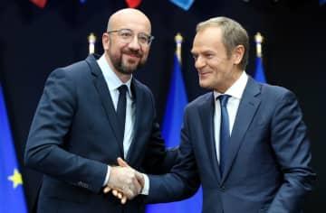 引き継ぎ式で握手を交わす、EU大統領のトゥスク氏(右)と次期大統領のミシェル氏=29日、ブリュッセル(ゲッティ=共同)